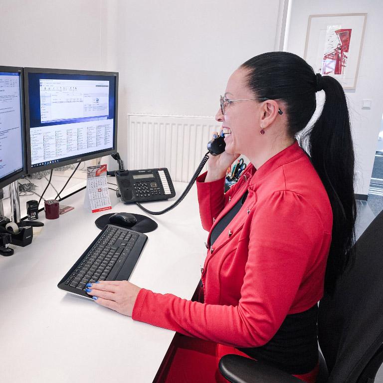 Empfangsdame sitzt vor dem Computer und telefoniert
